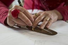 Руки на правителе кривой и бумаге вычерчивания ручки Стоковая Фотография RF