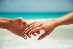 Руки на предпосылке воды бирюзы Женская рука в мужской руке стоковые изображения