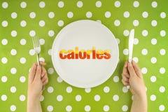 Руки на таблице с калориями на плите Стоковая Фотография RF