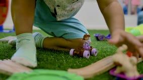 Руки небольшой детской игры на пластиковой игрушке сидя зеленая искусственная трава в комнате видеоматериал