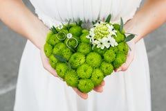Руки невесты держа валик для колец хризантемы в форме сердца Стоковое Изображение
