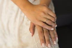 Руки невесты с кольцами и бежевым маникюром Стоковые Изображения