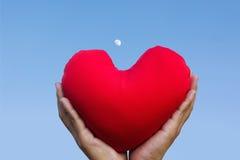 2 руки нежно поднимают и держат красное сердце с влюбленностью и уважают с предпосылкой неба Стоковые Фото