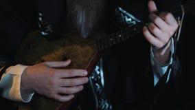 Руки непознаваемого человека играя историческое ussian balalaica внутри помещения сток-видео