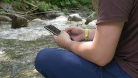 Руки непознаваемого Hiker мужские используя смартфон на предпосылке потока горы сток-видео