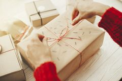 Руки оборачивая стильный подарок на рождество с красной лентой самомоднейше стоковые фотографии rf