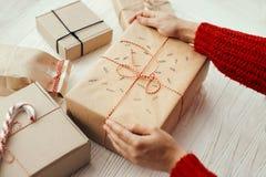 Руки оборачивая стильный подарок на рождество с красной лентой самомоднейше стоковое фото rf