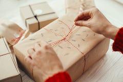 Руки оборачивая стильный подарок на рождество с красной лентой самомоднейше стоковая фотография