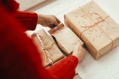 Руки оборачивая стильный подарок на рождество с красной лентой самомоднейше стоковые фото