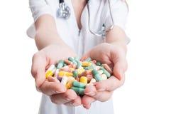Руки доктора женщины держа пук пилюлек Стоковое Фото
