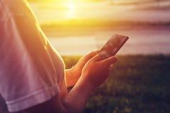 Руки отправляя СМС на мобильном телефоне в заходе солнца Стоковые Фото