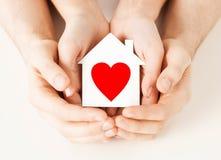 Руки пар держа дом белой бумаги Стоковые Изображения