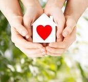 Руки пар держа дом белой бумаги Стоковое Изображение RF
