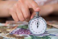 Руки персоны с секундомером и монетки над банкнотой Стоковая Фотография RF