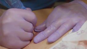 Руки перчаток кремния художника татуировки нося татуируют девушку в студии Взгляд замедленного движения видеоматериал