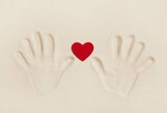 2 руки печатают в песке с красным сердцем Концепция символа для Стоковое Изображение RF