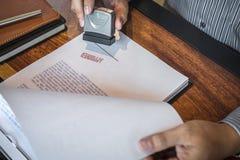 Руки печати бизнесмена на печатном документе для того чтобы одобрить договор подряда капиталовложений предприятий стоковое изображение
