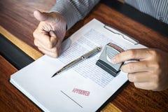 Руки печати бизнесмена на печатном документе для того чтобы одобрить договор подряда капиталовложений предприятий стоковые фотографии rf