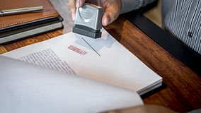 Руки печати бизнесмена на печатном документе для того чтобы одобрить договор подряда капиталовложений предприятий стоковые изображения rf