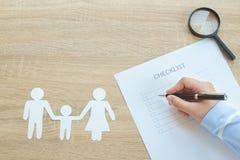 Руки писать контрольный списоок с ежегодным здоровьем семьи - для того чтобы сделать lis Стоковые Изображения RF