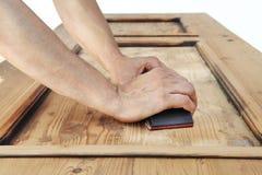 Руки плотника работают древесина с шкуркой Стоковые Фото