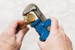 Руки поворачивая латунную гайку используя ключ для труб Стоковое Фото