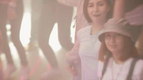 Руки повышения девушки брюнет на партии в ночном клубе среди другого танцы Фары видеоматериал
