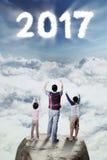 Руки повышения отца и детей на камне Стоковые Изображения RF