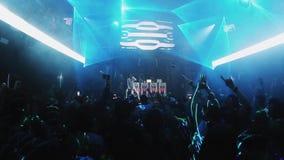 Руки повышения людей скачут на партию в ночном клубе Совершитель на этапе освещения видеоматериал