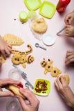 Руки подготавливают печенье снеговиков, конец-вверх праздника Пестротканые блюда младенца стоковая фотография rf