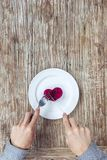 Руки подготавливая съесть сердце на плите стоковое фото