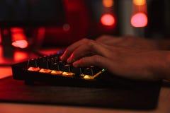 Руки подросткового мальчика gamer играя видеоигры на компьютере в da стоковые фотографии rf