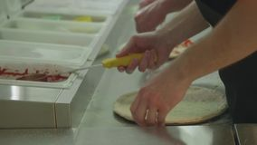 Руки 2 подростков положили дальше ingrediets на тесто и распространили томатный соус пока делающ пиццу сток-видео