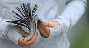 Руки подсчитывая деньги на запачканной предпосылке города Стоковая Фотография RF