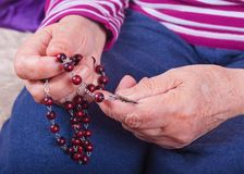 Руки пожилой женщины держа розарий стоковые фото