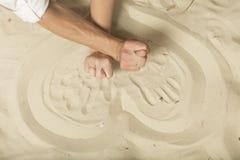 Руки показывая новобрачных смокв с кольцами на песке Стоковые Изображения