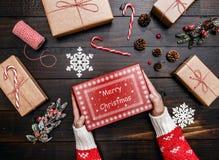 Руки показывая подарок на рождество Деревянная предпосылка с подарками Стоковые Фотографии RF