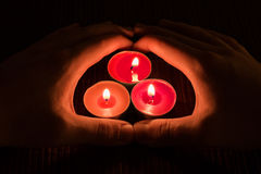 2 руки покрывая 3 горящих свечи Стоковое Изображение RF