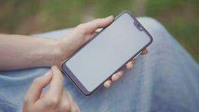 Руки пользы женщины печатая мобильные телефоны и экран касания работая со стилем приборов приложения винтажным в парке акции видеоматериалы