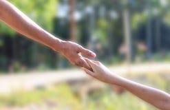 Руки помощи - рука сына отца hoding стоковые фото