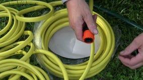 2 руки подготавливая соединение шланга воды на траве видеоматериал