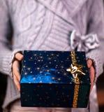 Руки предлагая красивый обернутый подарок Стоковые Изображения RF