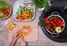 Руки прерывая желтый болгарский перец для vegetable салата - здоровье Стоковые Изображения