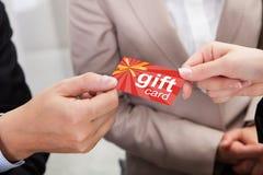 Руки предпринимателя давая карточку подарка к другому предпринимателю Стоковая Фотография