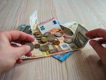 Руки принимая банкноты и монетки евро Стоковые Изображения RF