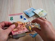 Руки принимая банкноты и монетки евро Стоковые Изображения