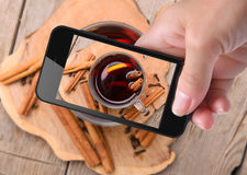 Руки принимая вино обдумыванное фото с smartphone Стоковые Фото