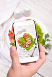 Руки принимая куриную грудку фото с smartphone стоковая фотография rf