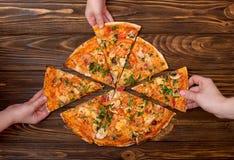 Руки принимая куски пиццы от деревянной предпосылки стоковые изображения