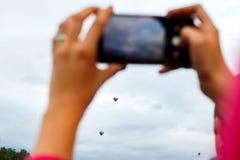 Руки принимая фото горячего воздушного шара на телефоне Стоковая Фотография RF